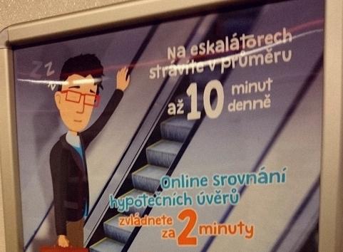 Reklama v metru, která říká: Na eskalátorech strávíte v průměru až 10 minut denně. Online srovnání hypotečních úvěrů zvládnete za 2 minuty.